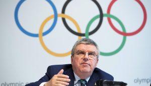 Thomas Bach falando em um microfone; fundo com o logo dos Jogos Olímpicos ao fundo