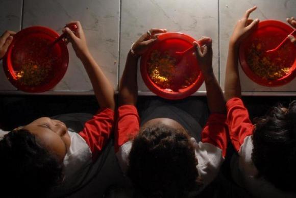 Crianças seguram prato de comida