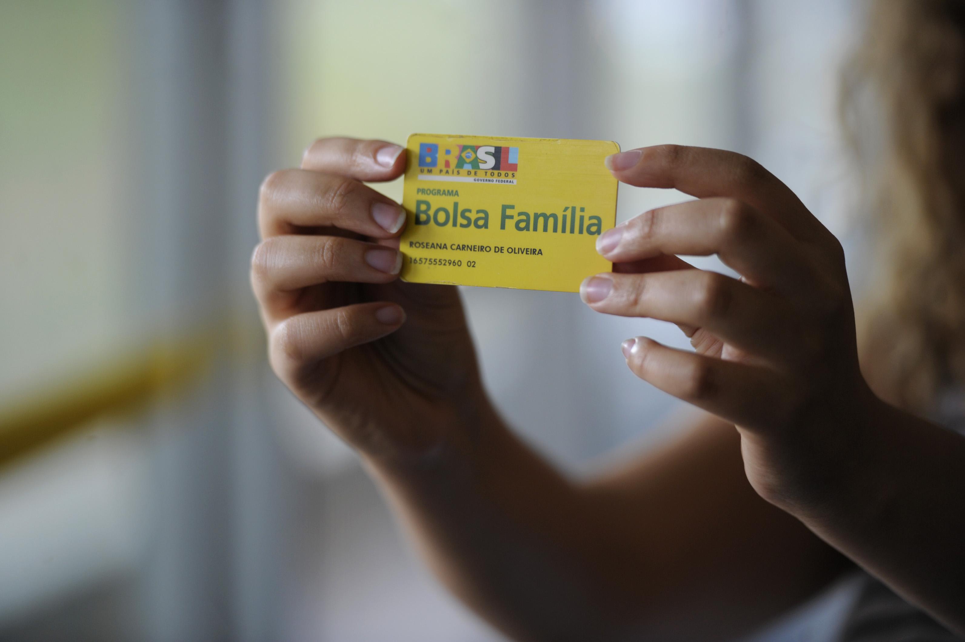 mão segurando cartão do Bolsa Família
