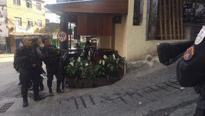 Policiais armados analisam local em ação na favela da Rocinha, no Rio de Janeiro