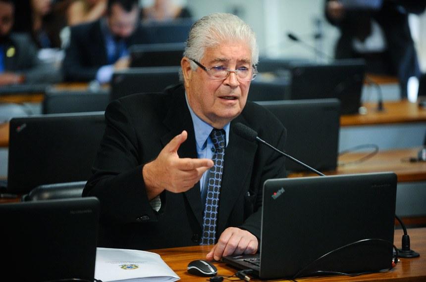 Senador Roberto Requião olhando para notebook e falando em microfone durante sessão no Senado