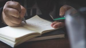 Mão escrevendo em um caderno