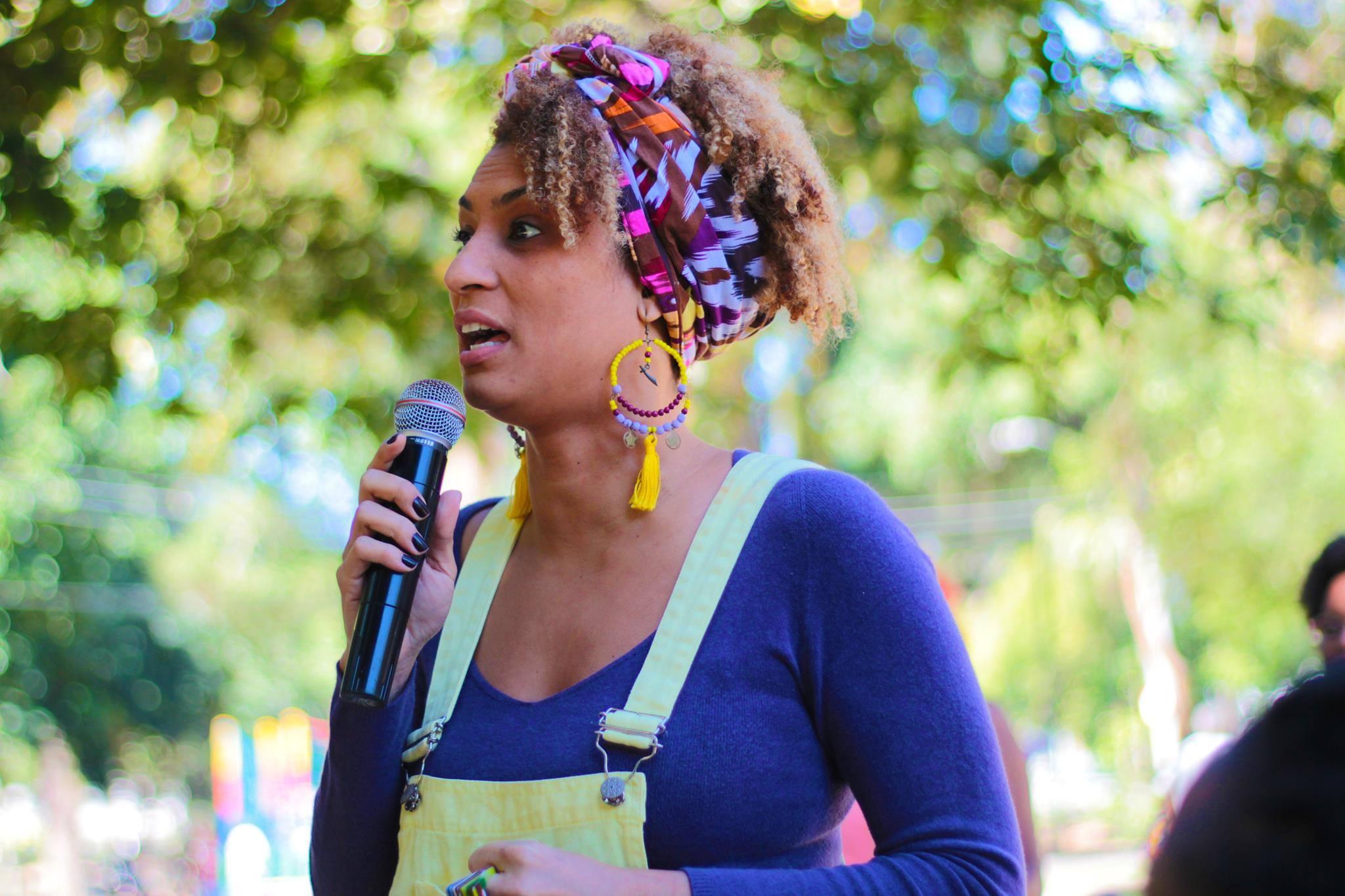 marielle franco falando em um microfone. Mulher negra de cabelos crespos castanhos, lenço colorido na cabeça e blusa azul