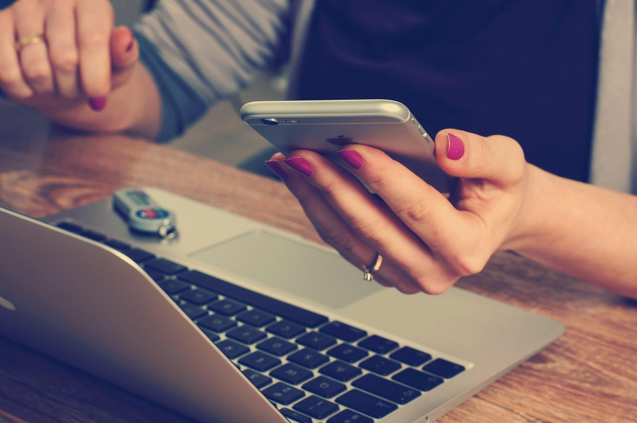 Pessoa usando computador e celular