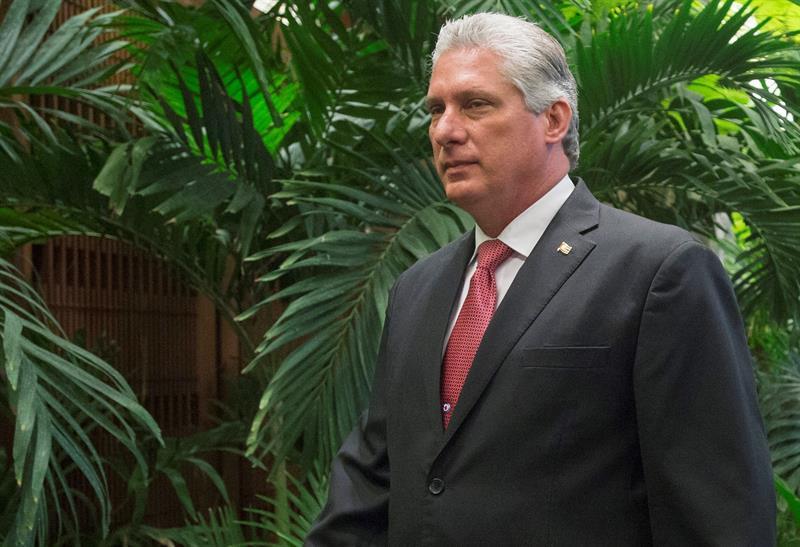 presidente de cuba, homem branco com cabelos brancos, gravata vermelha e terno preto, de pé em frente a folhas verdes