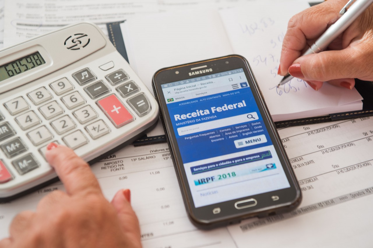 calculadora branca sendo manipulada pela mão de uma pessoa, celular aberto no site do Imposto de Renda e papel em branco sendo preenchido por uma mão segurando uma caneta