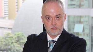 Homem branco careca de barba branca olha para a câmera. Usa terno e gravata colorida azul e preta