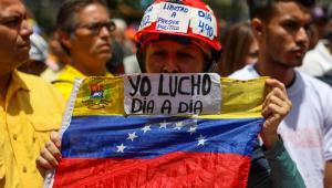 """Pessoa segurando uma bandeira da Venezuela escrito em espanhol """"eu luto dia a dia"""""""