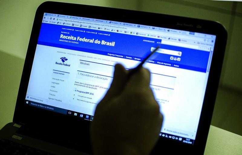 Pessoa segura uma caneca em frete um notebook aberto com a página da Receita Federal ao fundo