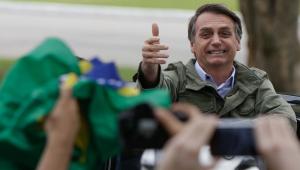 Jair Bolsonaro fazendo sinal de positivo com câmeras e bandeiras do Brasil