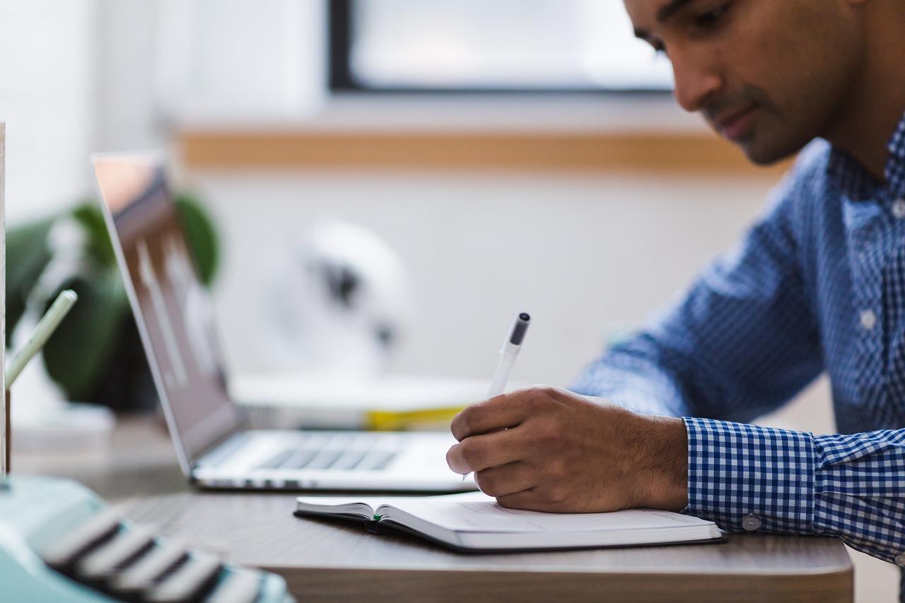 Homem escrevendo em um caderno com um notebook ao fundo