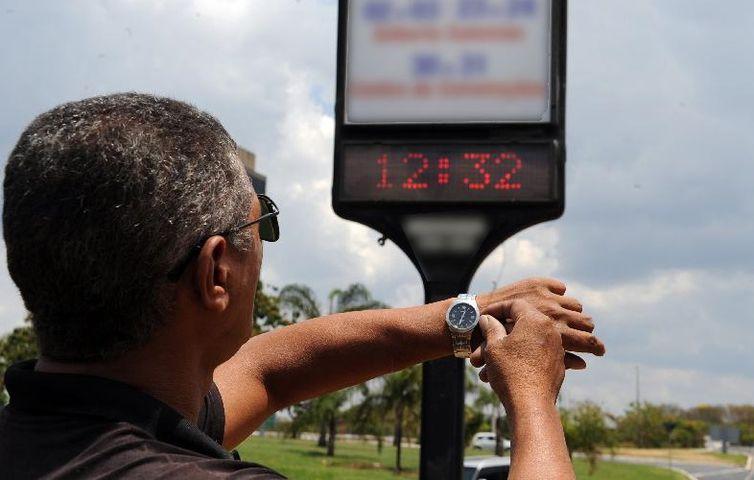 Homem olhando para o relógio de pulso; ao fundo, um relógio digital mostra a hora