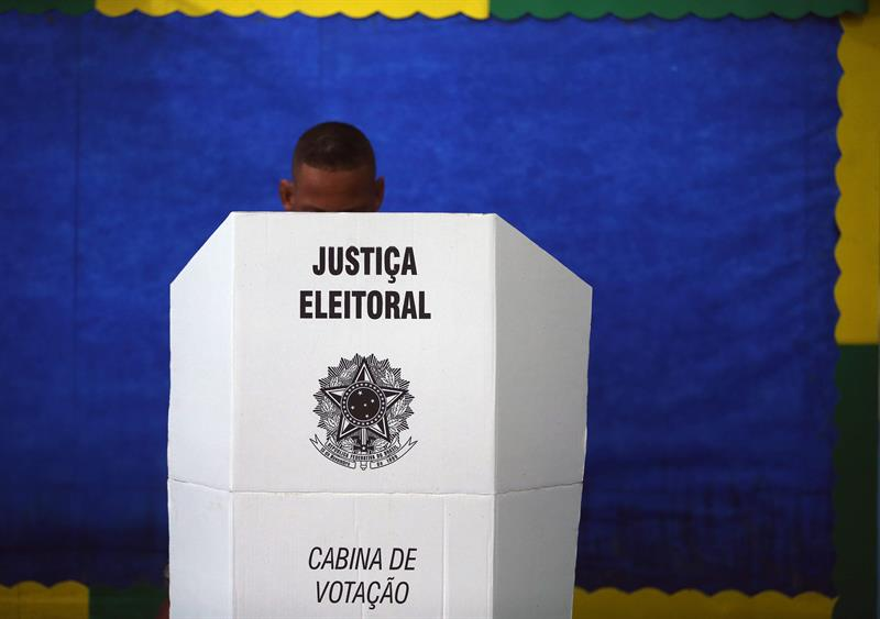 Pessoa votando de máscara em uma urna eleitoral