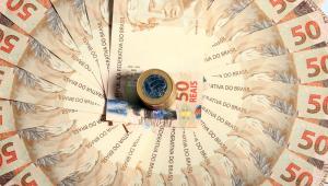 Moedas de um real em uma pequena torre e, ao redor delas, uma roda de notas de 50 reais