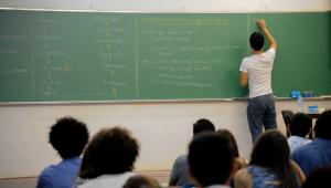 Professor de costas para alunos escrevendo na lousa