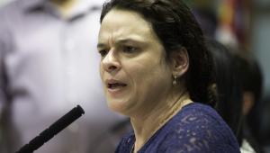 Deputada Janaina Paschoal falando em microfone. O rosto está focado, de perfil, a boca aberta e os cabelos longos e lisos para trás. Usa blusa de renda azul