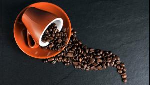 Grãos de café saindo de uma xícara laranja derrubada em cima de um pires