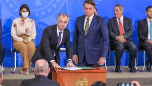 Ministro assina documento ao lado do presidente da República
