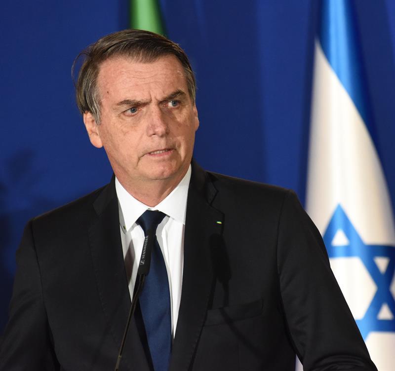 O presidente Jair Bolsonaro na frente de uma bandeira de Israel