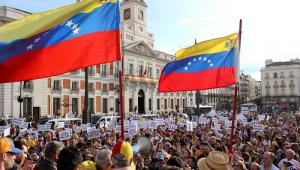 Pessoas agitando bandeiras da Venezuela durante um protesto