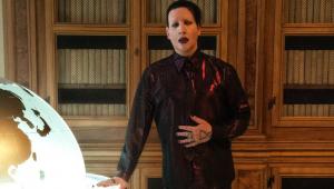 Marilyn Manson com um terno de couro preto, batom e cabelos pretos, com uma das mãos em cima do terno e outra em cima da mesa. Atrás, uma estante de madeira de livros