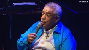 Agnaldo Timóteo usando uma camiseta azul e cantando