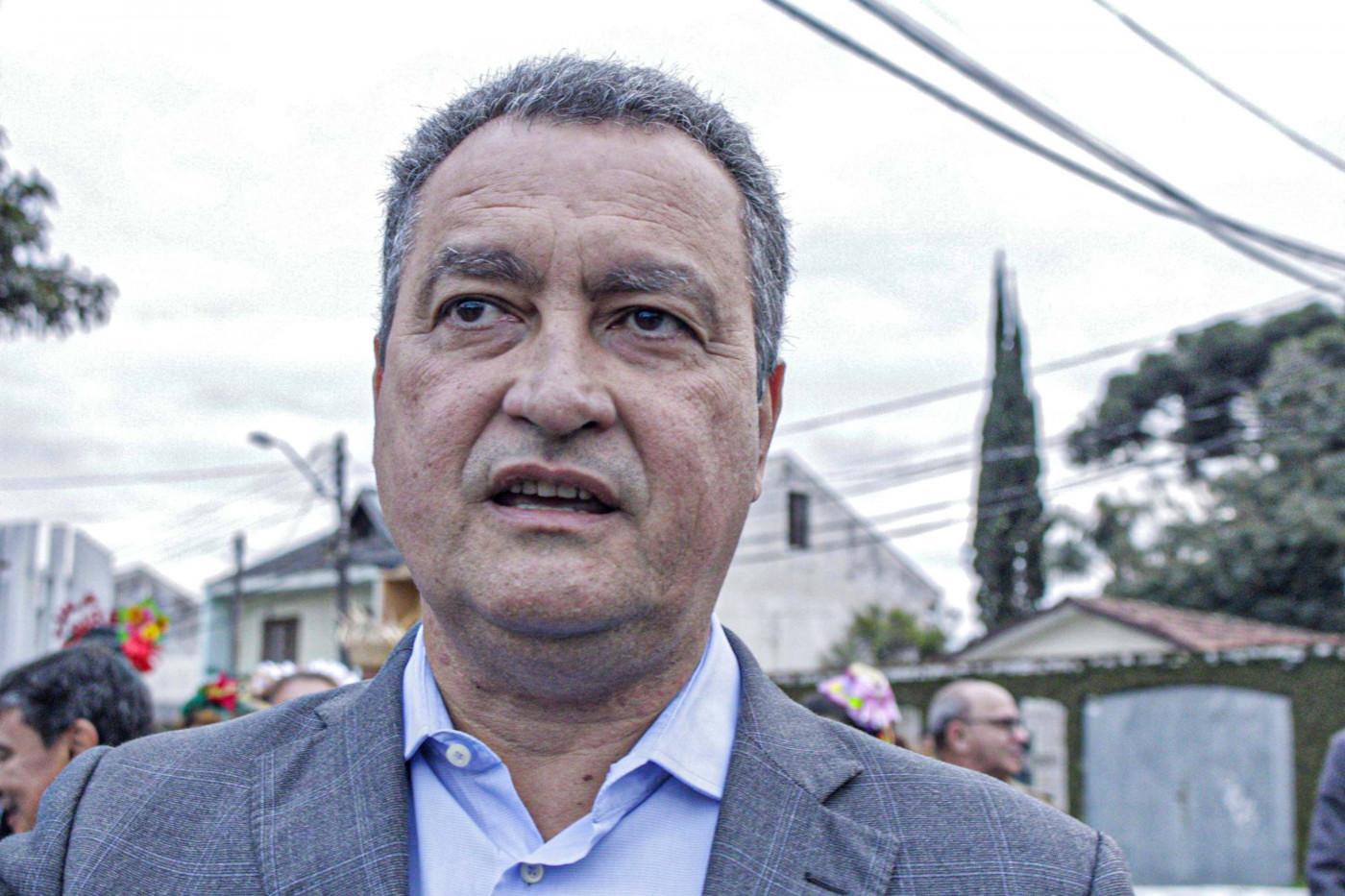 governador da Bahia, Rui costa, em foto de busto, olhando para a frente. Homem branco de camisa social azul e terno cinza