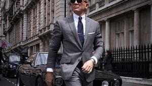 James Bond, homem caminhando de óculos, terno cinza e gravata azul.