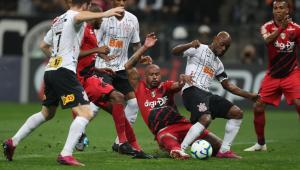 Jogadores do Corinthians e Athletico PR em volta da bola. Um está caido, enquanto outros cinco fazem manobras em volta