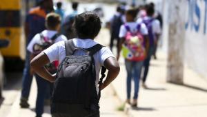 grupo de alunos caminha com mochila nas costas