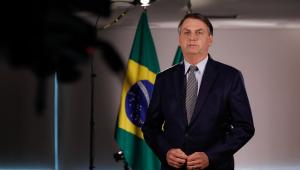 O presidente Jair Bolsonaro em pé em frente a uma bandeira do Brasil