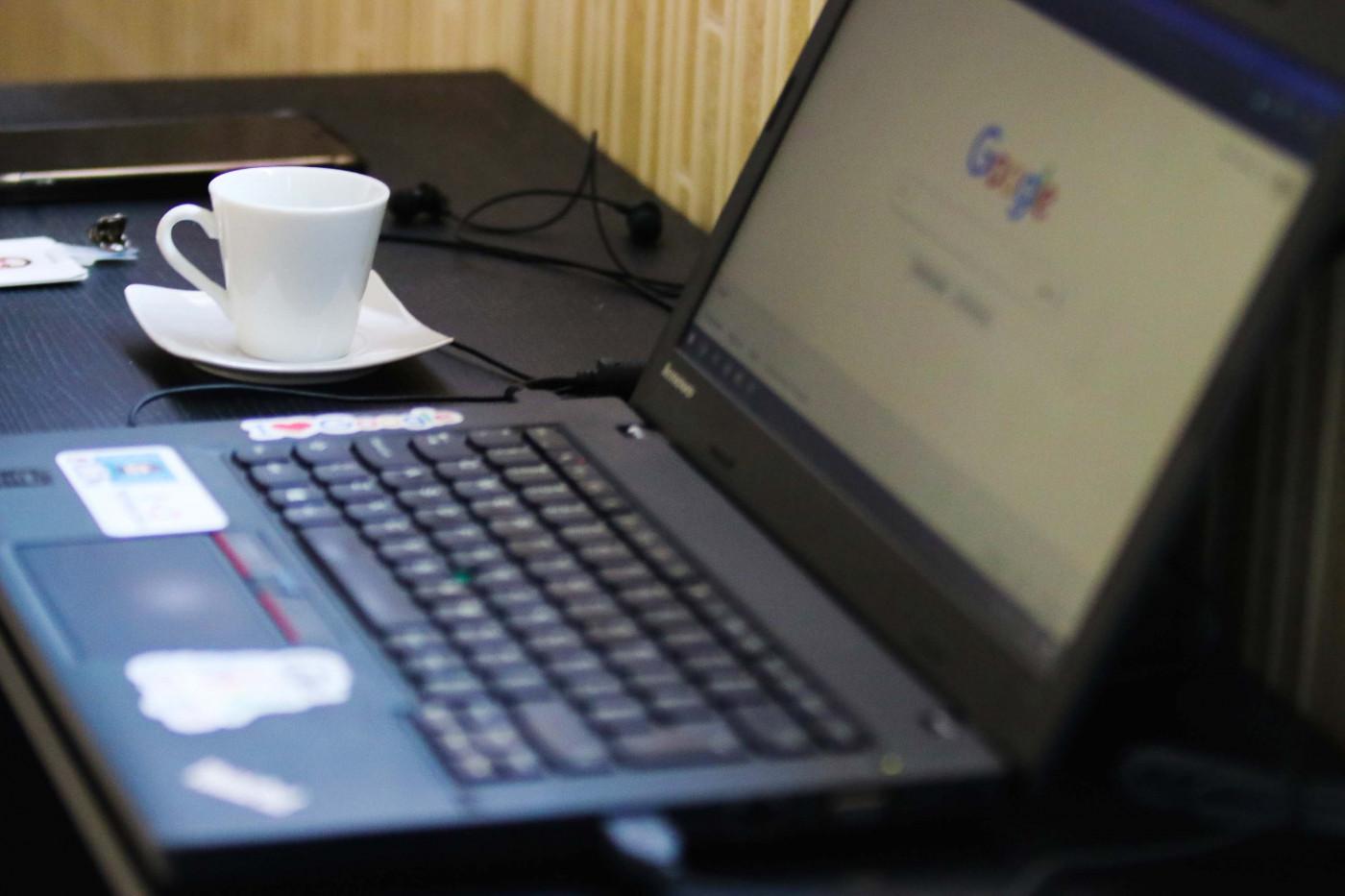 notebook aberto com xícara branca de café ao longo. página do google no desktop