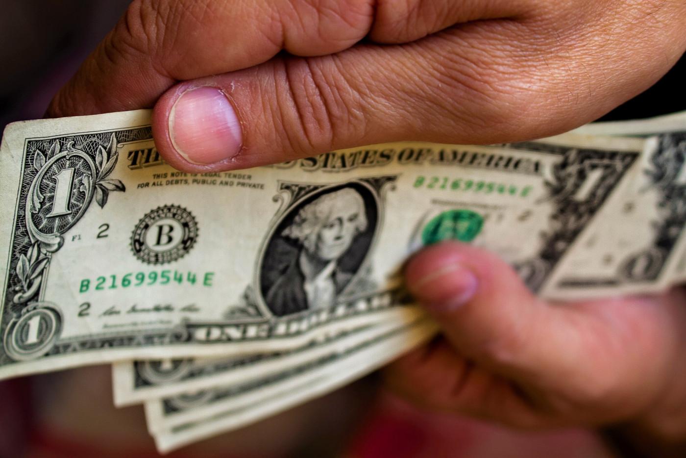 Mão segura notas de dólar