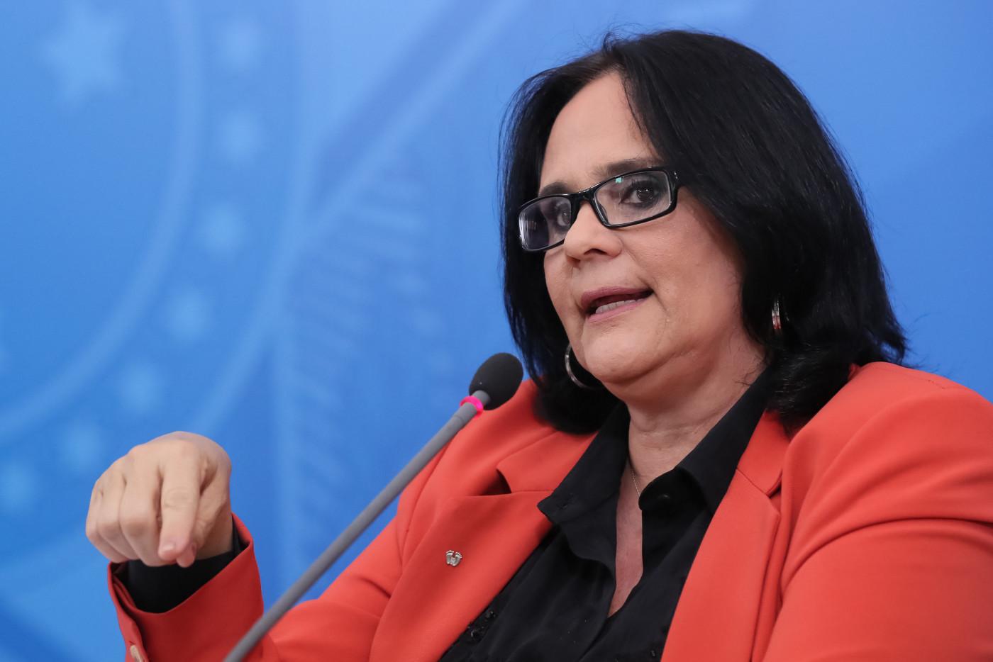 ministra damares alves. mulher branca de cabelo chanel preto, falando ao microfone, com casaco vermelho