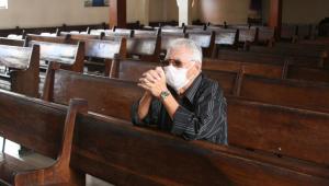 Homem reza de máscara em igreja