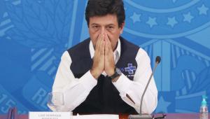 Ministro Luiz Henrique Mandetta com as mãos fechadas como se estivesse rezando. Ele usa camisa branca e um colete azul marinho do SUS. Fala em uma coletiva, está em cima de uma mesa de madeira, com um fundo azul e um microfone.