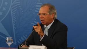 Paulo Guedes, ministro da Economia, fala com o dedo em riste, sentado à frente de um fundo azul