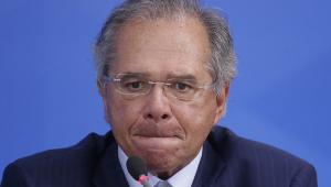 Paulo Guedes, homem idoso de óculos e cabelos grisalhos, com a boca apertada falando em frente a um microfone