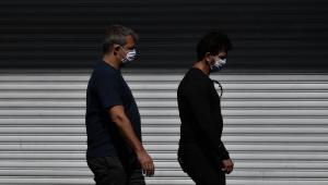 Pessoas caminham de máscara pelas ruas de São Paulo