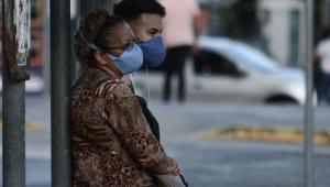 Duas pessoas com máscaras de proteção contra a Covid-19 na rua