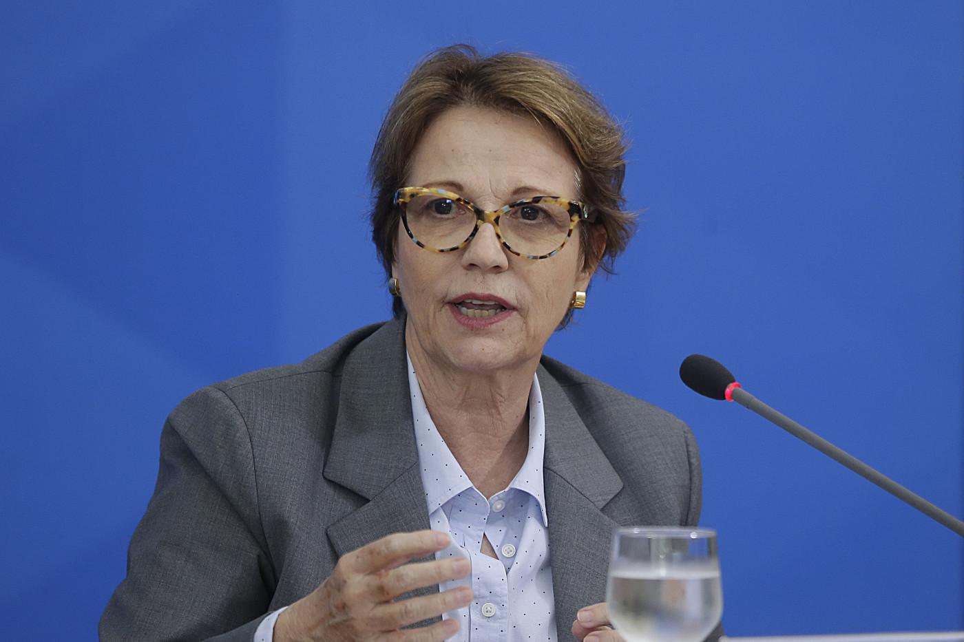 Mulher de cabelos curtos e óculos com armação grossa fala em microfone diante de um fundo azul
