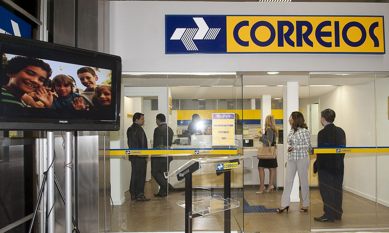 Fila de pessoas dentro de uma agência dos correios, divididas por faixas amarelas e sob a logomarca da empresa em amarelo e azul