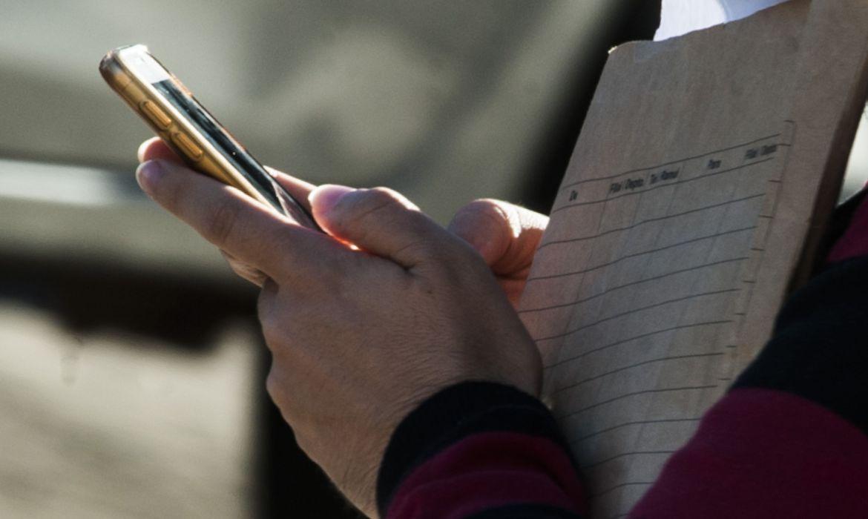 Pessoa com caderno e celular na mão
