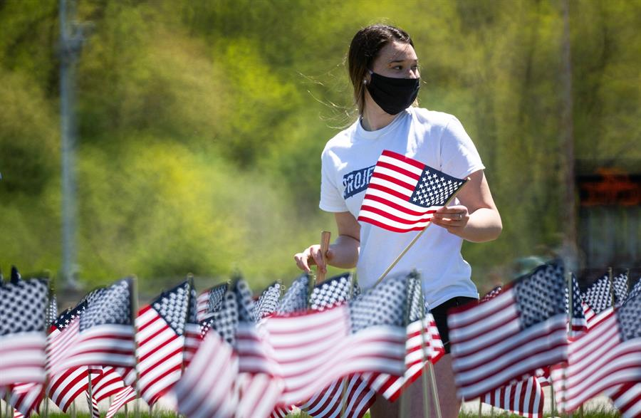 Mulher usa camiseta branca, máscara de proteção preta e segura uma bandeira dos EUA