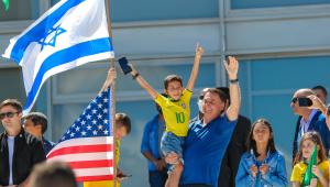 Bolsonaro, homem com criança no colo com camiseta do Brasil acenando. Ao lado uma menina e bandeiras dos EUA e de Israel