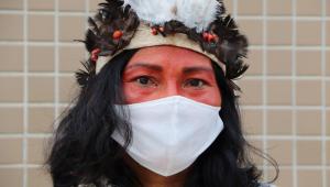Mulher indígena usando máscara