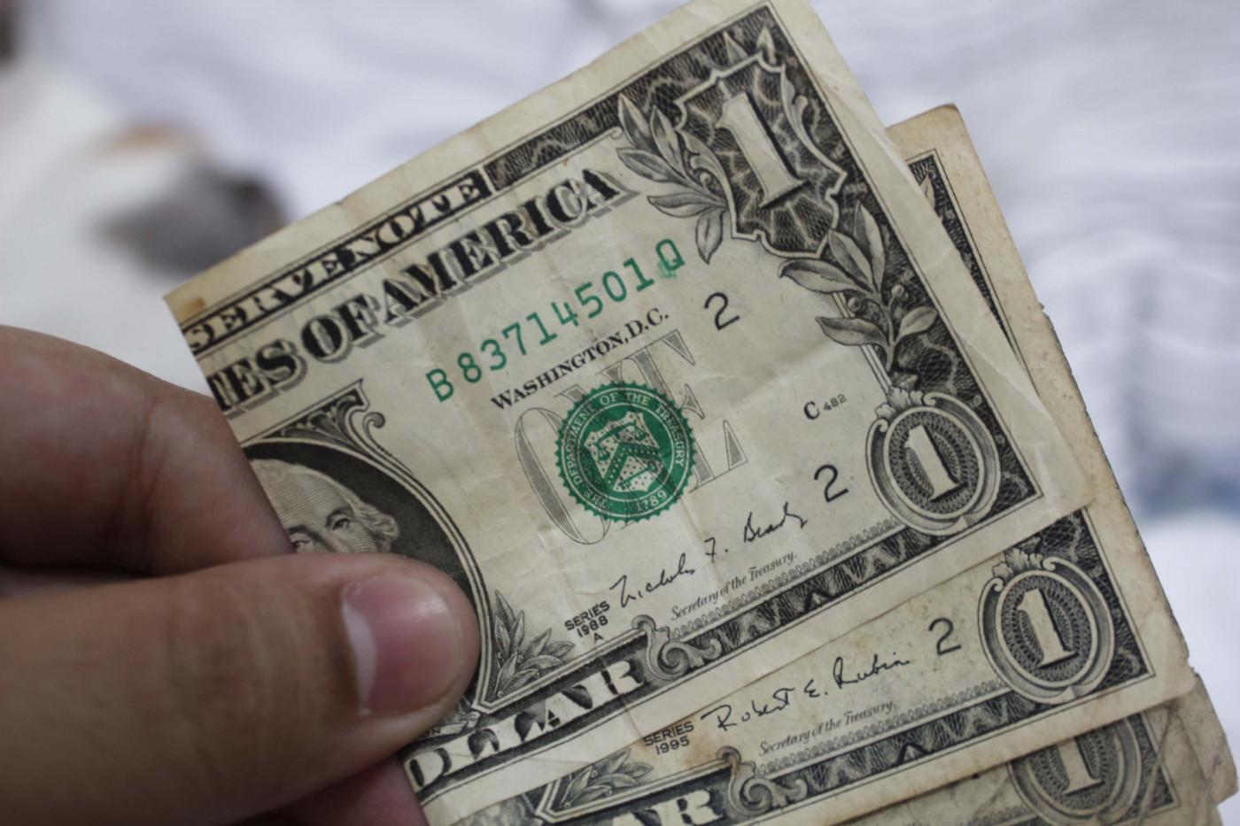 Dólar recua com bom humor no exterior, mas segue pressionado por turbulências políticas e risco fiscal