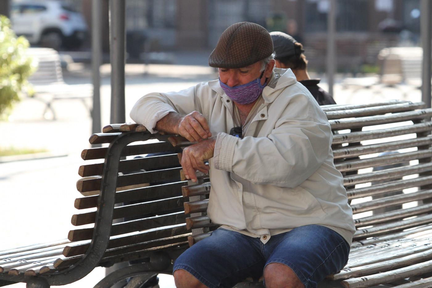 Idoso sentado em banco de uma praça usando máscara de proteção