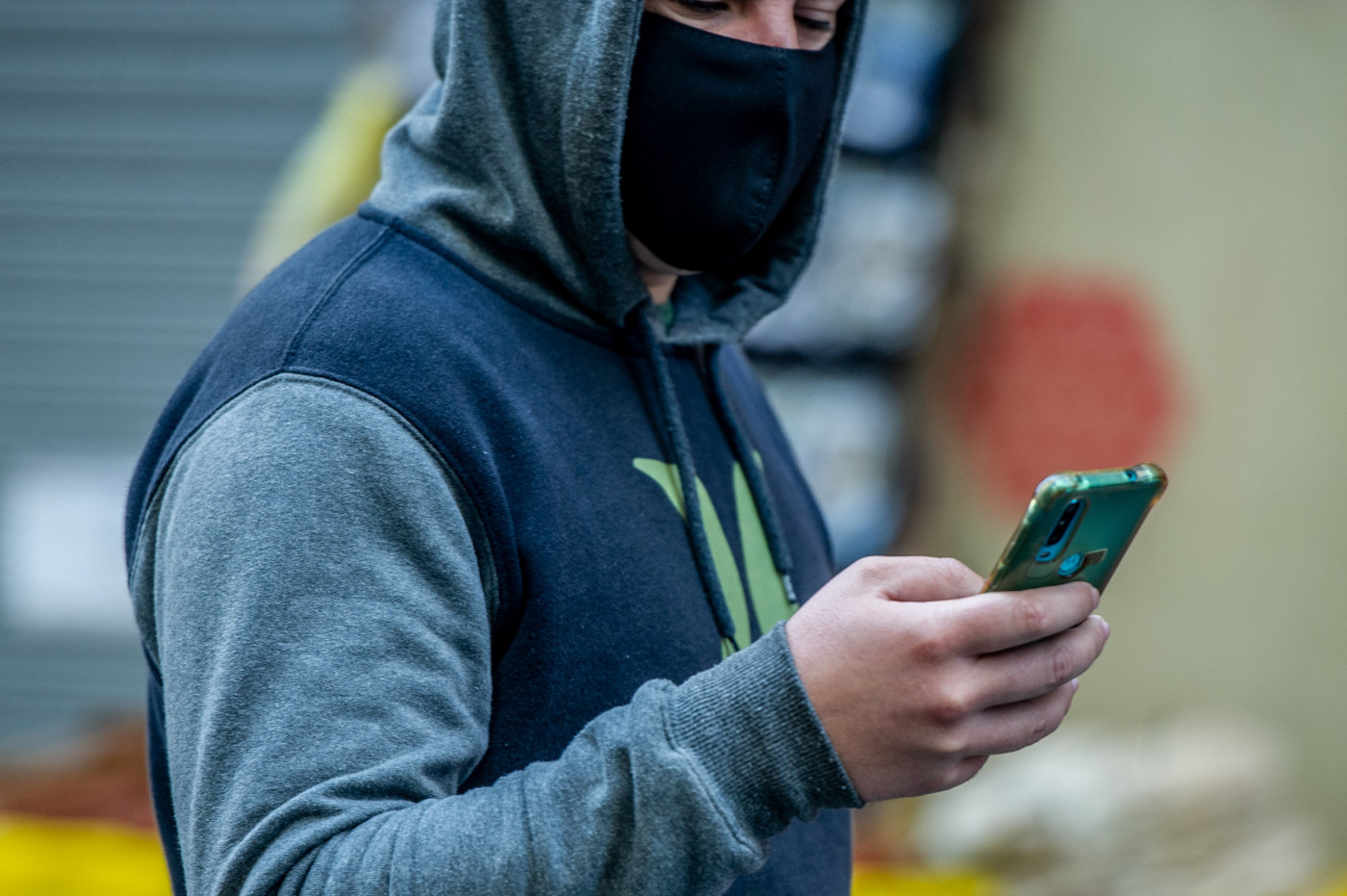 Usando máscara para se proteger do coronavírus, homem mexe no celular