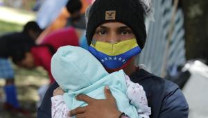 homem com máscara da bandeira da venezuela segura um bebê no colo